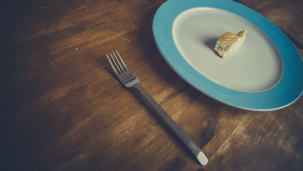 fork, plate, and small piece of bread on wooden table