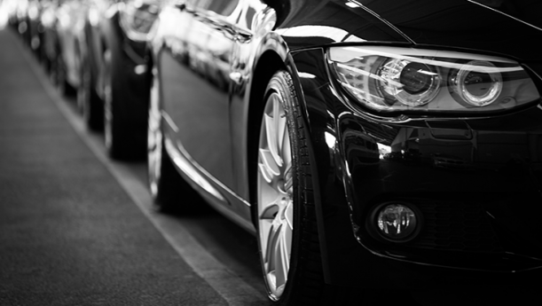 black and white photo of new cars in line on the street