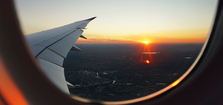 looking out of airplane window at sunset
