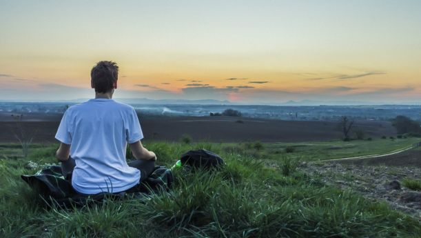 Man meditating on a hill