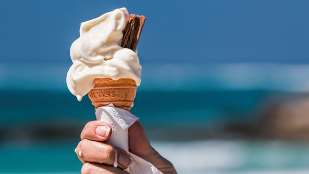 man holding melting ice cream cone at beach
