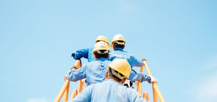 men with hardhats walking up stairway