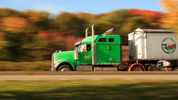 green truck driving on highway during fall