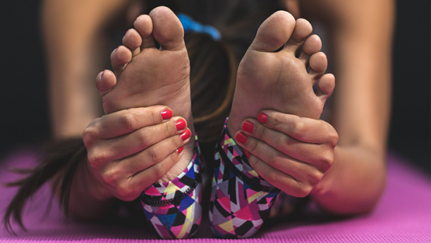 woman stretching for yoga and reaching for her feet