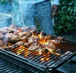 Grill with chicken cooking over a flame